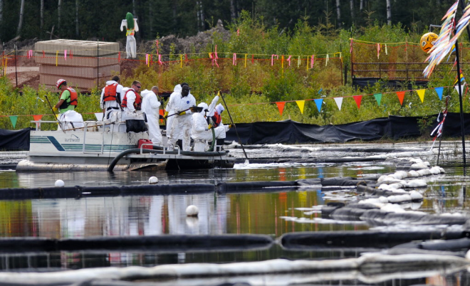 Canadian Natural Resources Limited workers cleaning up the bitumen spill in 2013 after it seeped up through a fissure at their Primrose oil sand projects north of Cold Lake. Alta. ~ Ed Kaiser/Edmonton Journal